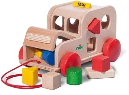 Houten taxi die kan getrokken worden met een rood koordje. De motorkap is half open, er zijn twee houten blokjes zichtbaar erin. In de wanden van de taxi zijn verschillende openingen met verschillende geometrische vormen, rond de taxi en in één van de openingen liggen 6 houten blokken van verschillende vormen en kleuren.