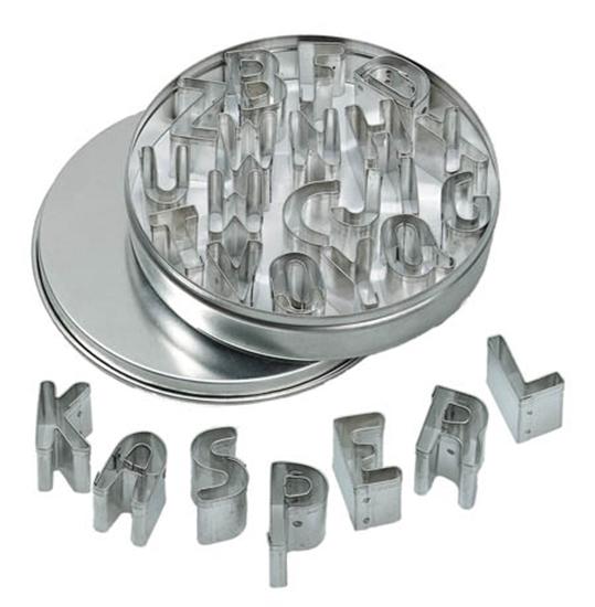 Een metalen ronde doos ligt open op zijn deksel. De doos ligt vol met metalen uitsteekvormen in de vorm van alle letters van het alfabet. Onderaan de doos liggen de volgende letters in een halve cirkel gespreid: k a s p e r l.