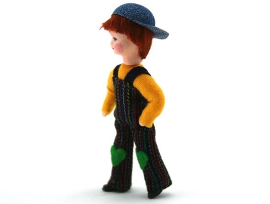 Pop voor poppenhuis, jongen met gele trui, donkere overal en een pet in jeans stof, achterste voor gedragen.