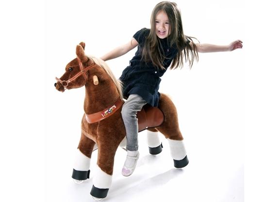 Zacht bruin speelpaard met witte enkels. Op zijn rug rijdt een meisje  met donkerblauw kleed en lange bruine haren.