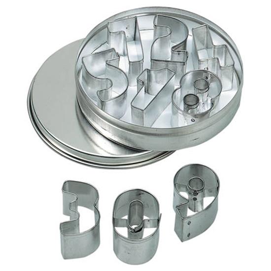 Een metalen doos is open en rust op haar deksel. Voor de doos liggen 3 uitsteekvormpjes:  3 0 9. In de doos liggen de andere uitsteekvormpjes  1 2  4 5 6 7.