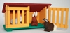 Red, green and yellow rabbit cage with one of the two  doors open, a small light brown wool rabbit in the cage, a dark brown rabbit in front of the cage.