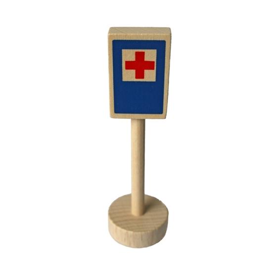 Houten verkeersteken hospitaal. Rechthoekig blauw planeel met rood kruis op een houten paal en ronde houten sokkel.