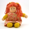 Rag doll with long red hair and blue eyes. She wears a yellow gown printed with red flowers.