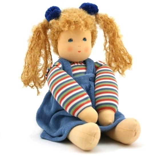 Voddenpop met blauwe ogen en twee blonde staartjes met blauwe strikjes. Ze zit met haar armen op haar schoot. Ze draagt  een blauw-wit-rood-groen gestreepte sweatshirt en een overgooier in blauwe fluweel.