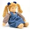 Poupée de chiffon aux yeux bleus, les cheveux blonds  attachés en deux queues par des rubans bleus. Elle porte un sweatshirt rayé bleu blanc rouge vert et une robe chasuble en velours bleu. Elle est assise, les bras disposés à côté d'elle.