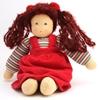 Poupée de chiffon assise, ayant des cheveux brun foncé en laine, montés en deux queues avec des rubans rouges. Elle a des yeux bleus peints à la main et porte une robe en velours rouge et un sweatshirt rayé.