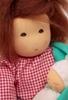 Close up du visage d'une poupée de chiffon aux cheveux de mohair brun et aux yeux bruns, portant son bébé dans las bras. Elle porte une blouse à carreaux rouge et blanc.