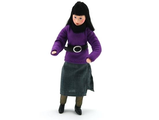 Pop voor poppenhuis, klassieke moeder met zwart lang haar, grijze rok, paarse trui met bovenop de trui een brede zwarte ceintuur met grote gesp.