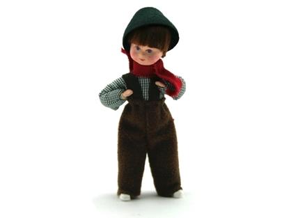 Pop voor poppenhuis, jongen met groen geruit hemd, donker bruine wollen hoed en broek met bretellen en een rode sjerp.