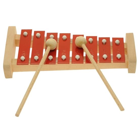 Pentatonische xylofoon gemaakt van een massief  beuken houten kader waarop  8 rode metalen plaatjes liggen met twee stokjes met een houten bol op het uiteinde om er muziek op te maken.