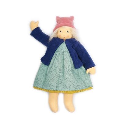 Voddenpop met blauwe ogen en blond mohair haar gekleed met een groen kleed met blauwe stipjes,  een dikke blauwe vest en een roos wollen mutsje. Ze staat recht en houdt één hand in de lucht.