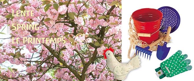 Japanse kerselaar in bloei met daarnaast een metalen zand speelset, groene kindertuinhandschoenen en een wit vilten kipje.
