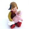 Une poupée-fillette pour maison de poupée est assise par terre. Elle tient sur ses genoux une poupée au pantalon blanc et pullover rose. La poupée porte un pull à manches longues vert pomme et une salopette au couleurs bariolées. Elle a des yeux bleus et des cheveux blonds retenus de côté par un ruban bleu vif.